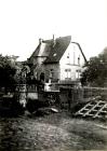 Eine gepflasterte Straße mit dem alten Pfarrhaus im Hintergrund