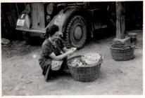 Anna Fries schaelt vor einem Fahrzeug der deutschen Wehrmacht Kartoffeln